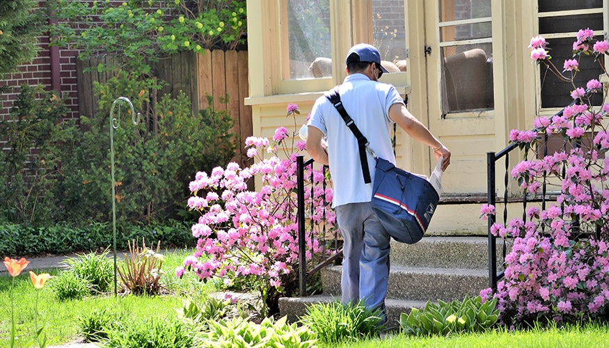 postal worker delivering mail to home